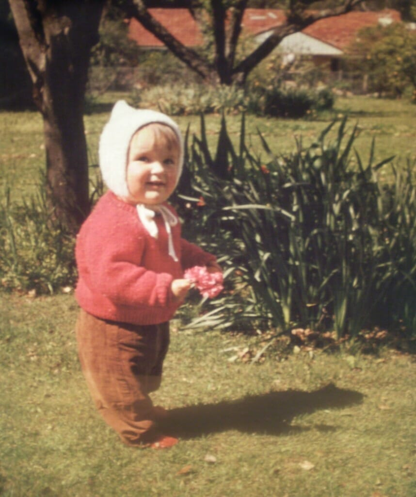 This was me as a toddler picking flowers near one of the many fruit trees in our backyard