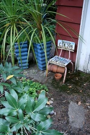 This quirky recycled numberplate chair is not only a place to sit but adds character as garden art! Clever use of repetition with the 2 blue pots and matching plants brings harmony to this tiny space. Photo: Gardening in a Minute