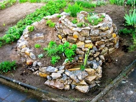 Herb spiral planted out with a pond. | The Micro Gardener